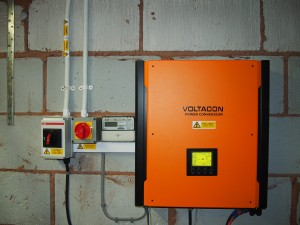 The inverter mounted on the wall of the garage with the feed in tariff meter.